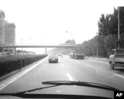 送方励之去机场的车行驶在建国门外大街上。车前有警车开路。