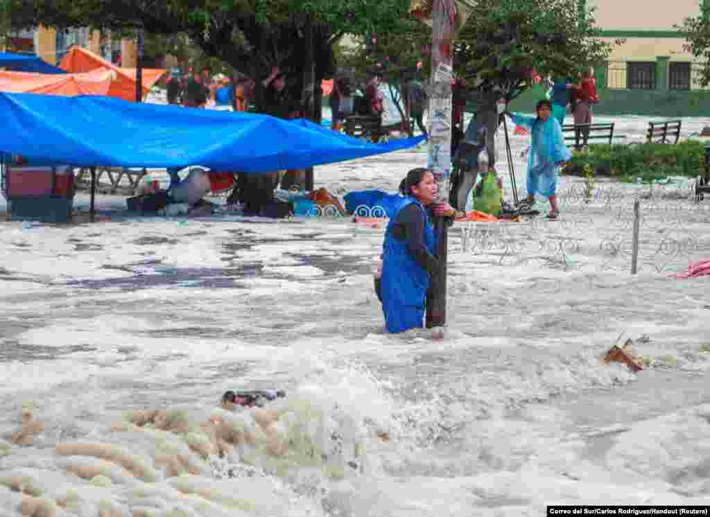 A woman clings to a lamp post during flooding caused by heavy rains in Sucre, Bolivia, January 4, 2021.