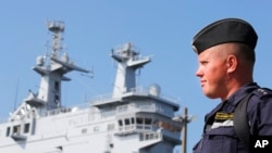 FILE - A Russian sailor stands next to the Vladivostok warship in the port of Saint-Nazaire, western France.