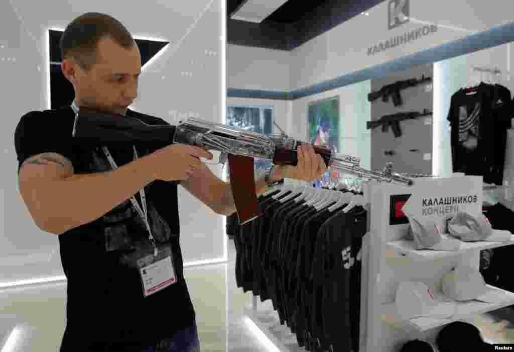 អ្នកលក់ម្នាក់បង្ហាញពីការបាញ់កាំភ្លើង AK-47 នៅហាងលក់វត្ថុអនុស្សាវរីយ៍ Gunmaker Kalashnikov ដែលទើបតែបើកមួយនៅក្នុងព្រលានយន្តហោះ Sheremetyevo ក្នុងក្រុងមូស្គូ ប្រទេសរុស្ស៊ី កាលពីថ្ងៃទី២២ ខែសីហា ឆ្នាំ២០១៦។
