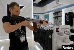 A salesperson demonstrates a model AK-47 assault rifle at the newly opened Gunmaker Kalashnikov souvenir store in Moscow's Sheremetyevo airport, Russia, August 22, 2016.