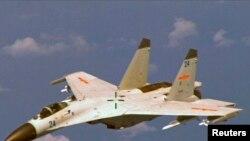 Sebuah jet tempur J-11 China terlihat terbang di dekat P-8 Poseidon Angkatan Laut AS sekitar 215 km timur Pulau Hainan China dalam foto selebaran Departemen Pertahanan AS yang diambil pada 19 Agustus 2014. (Foto: Reuters)