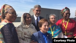 """Renowned hollywood actor George Clooney takes a group photo with a group of women during his visit to attend global forum of """"Against the Crime of Genocide"""" in Armenia in late April, 2016. (Photo supplied by Youk Chhang)"""