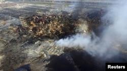 Foto menunjukkan asap membumbung dari puing peti kemas pengiriman di lokasi ledakan minggu lulu di Tianjin, China, 15 Agustus 2015.