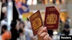 资料照:一名香港抗议者手举英国国民(海外)护照抗议港版国安法。(2020年6月1日)