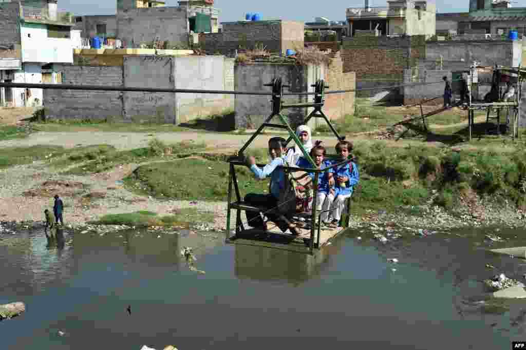 Anak-anak sekolah Pakistan menyeberangi danau kecil dengan kereta gantung untuk berangkat ke sekolah di pinggiran Islamabad.