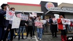 Para pekerja berunjuk rasa di luar restoran Burger King di Charlotte, North Carolina, Kamis (5/12), menuntut kenaikan upah. (AP/Chuck Burton)
