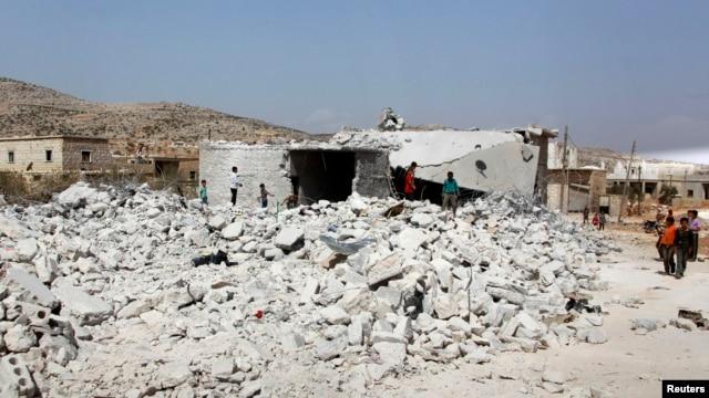 Cư dân gần một tòa nhà bị phá hủy trong các cuộc không kích của Hoa Kỳ và liên minh tại Kfredrian, tỉnh Idlib, Syria, ngày 24/9/2014.