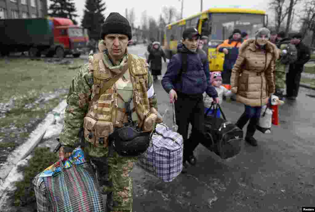 A member of the Ukrainian armed forces assists local residents onto a bus to flee the military conflict, in Debaltseve, eastern Ukraine. Convoys of buses converged from two sides on the town  after separatist rebels and government forces appeared to have patched together a truce to allow civilians to be evacuated.