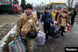 FILE - A member of the Ukrainian armed forces assists local residents onto a bus to flee the military conflict, in Debaltseve, eastern Ukraine, Feb. 6, 2015.
