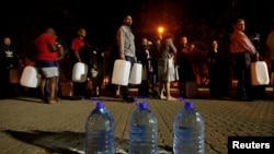 FILE - People queue to collect water from a spring in the Newlands suburb as fears over the city's water crisis grow in Cape Town, South Africa, Jan. 25, 2018.
