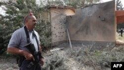Сотрудник израильской службы безопасности стоит у дома в киббуце Киссуфим, пострадавшего в результате обстрела.