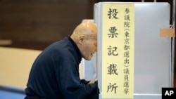 A voter selects candidates before casting a ballot in Japan's upper house parliamentary elections at a polling station in Tokyo, Sunday, July 10, 2016.