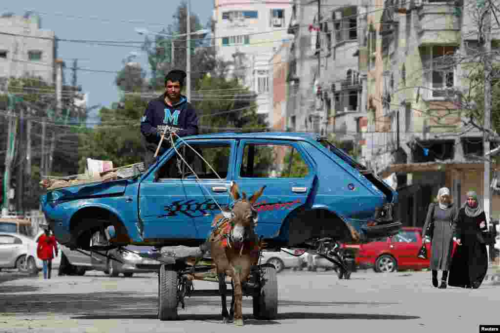 A Palestinian man rides a donkey-drawn cart transporting an old car to a scrap yard, in Gaza City.