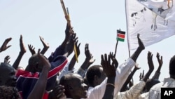 """FILE - Residents wave and cheer """"Bye Bye Bashir"""" - referring to Sudan's President Omar al-Bashir - after the result of an unofficial vote was announced in the disputed border region of Abyei, whose ownership is claimed by both Sudan and South Sudan, Oct. 31, 2013. (AP)"""