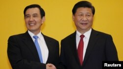 FILE - Chinese President Xi Jinping shakes hands with Taiwan's President Ma Ying-jeou during a Nov. 7, 2015, summit in Singapore. Leaders of political rivals China and Taiwan met Saturday for the first time in more than 60 years.