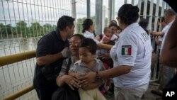 Mama mhamiaji wa Honduras na mtoto wake wakivuka daraja baada ya kuvuka mpaka ulioko kati ya Guatemala and Mexico, katika mji wa Ciudad Hidalgo, Mexico, Octoba 20, 2018.