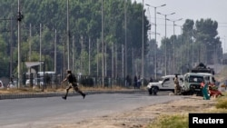 An Indian army soldier runs for cover at the scene of an encounter with separatist militants in Srinagar, June 24, 2013.