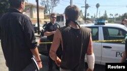 Polisi berbicara dengan korban penikaman dekat protes Klu Klux Klan di Anaheim, California, 27 Februari 2016. Setidaknya tiga orang ditikam, satu di antaranya luka parah, ketika anggota KKK dan kelompok kontra-demonstran bentrok.
