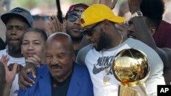Lebron James de Cavaliers de Cleveland, avec le trophée du champion de la NBA 2016, tient à l'épaule Brown 'Jim Brown, un ancien de l'équipe, à Cleveland, 22 juin 2016.