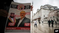 """A man holds a poster showing images of Saudi Crown Prince Muhammed bin Salman (L), dubbed """"assassin,"""" and of journalist writer Jamal Khashoggi, dubbed """"martyr,"""" during a prayer service for Khashoggi, in Istanbul, Turkey, Nov. 16, 2018."""