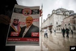 "A man holds a poster showing images of Saudi Crown Prince Muhammed bin Salman and of journalist writer Jamal Khashoggi, describing the prince as ""assassin"" and Khashoggi as ""martyr"" during funeral prayers in absentia for Khashoggi who was killed at the Saudi consulate in Istanbul on Oct. 2, 2018."