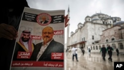 "A man holds a poster showing images of Saudi Crown Prince Muhammed bin Salman and of journalist writer Jamal Khashoggi, describing the prince as ""assassin"" and Khashoggi as ""martyr"" during funeral prayers in absentia for Khashoggi in Istanbul, Nov. 16, 2018."