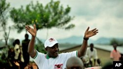 Burundian President Pierre Nkurunziza waves to supporters at the end of a political rally in Rugombo, northern Burundi, 14 May 2010