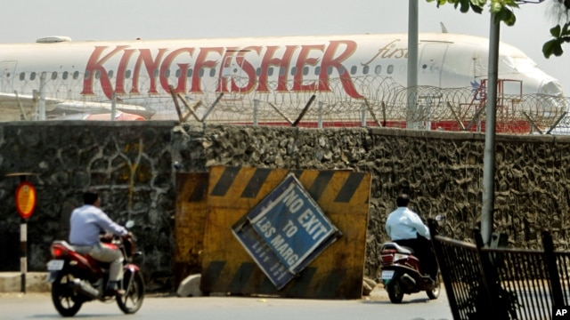 Commuters drive past a stationary aircraft belonging to Kingfisher airlines at the domestic airport in Mumbai, India, March 20, 2012.