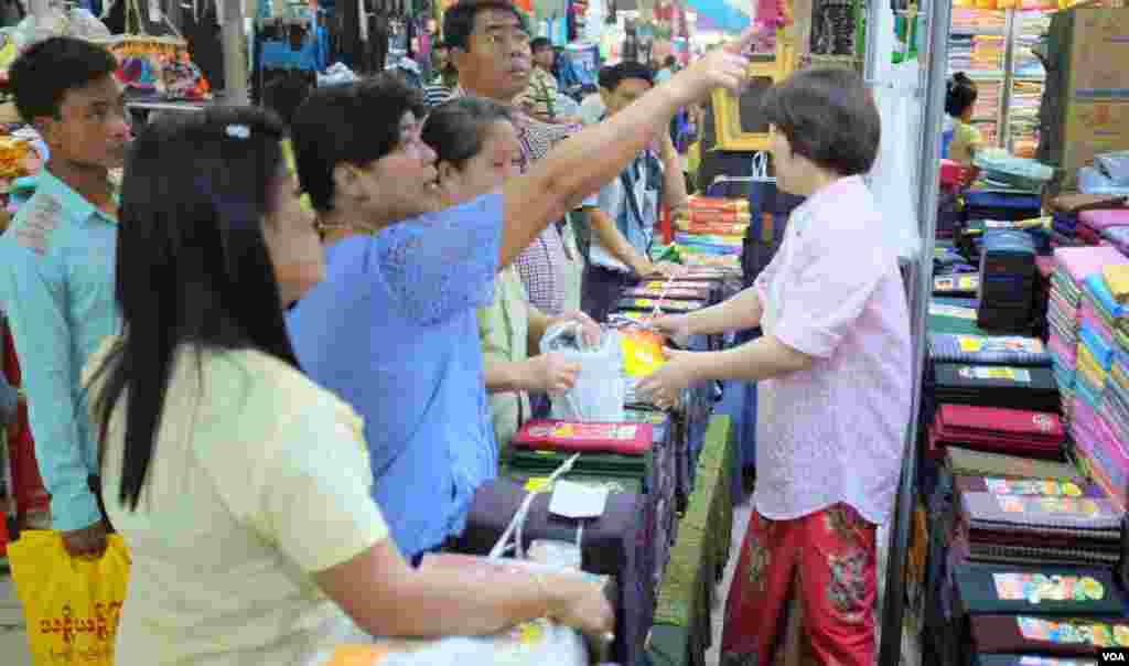 Shoppers in Yangon looking at longyi for sale. (Steve Herman/VOA News)