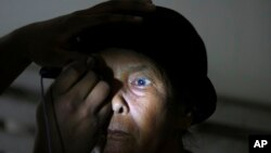 FILE - A patient has an eye exam at a military hospital in Padang Sidempuan, North Sumatra, Indonesia, Nov. 3, 2012.