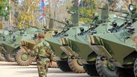 A Cambodian soldier walks past armored vehicles during the National Assembly members' visit to troops in a military base near the Preah Vhear temple in Preah Vihear province, some 500 kilometers northwest of Phnom Penh, February 9, 2011.