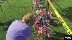一名妇女在美国田纳西州查塔努加枪击现场附近哀悼丧生的四名海军陆战队队员。一名海军士官后来伤重不治而死。(美国之音贝恩拍摄)