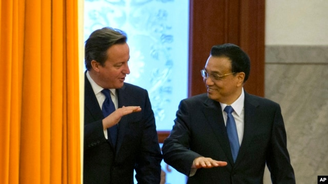 British Prime Minister David Cameron, left, chats with Chinese Premier Li Keqiang as they arrive for a welcome ceremony at the Great Hall of the People in Beijing, China, Monday, Dec. 2, 2013.
