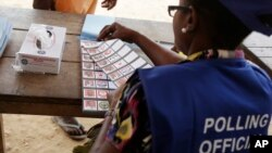 An electoral official tears a presidential ballot paper during the Presidential and parliamentary election, in Kibi, eastern Ghana, Dec. 7, 2016.