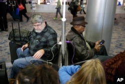 In this Dec. 29, 2014, photo, people use a charging station at McCarran International Airport in Las Vegas.