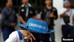Seorang pekerja mengenakan topi saat mengikut demonstrasi menentang rencana pemerintah merevisi Undang-Undang Ketenagakerjaan, di luar gedung DPR/MPR, Jakarta, 20 Januari 2020. (Foto: Reuters)
