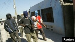 FILE - Haitian vigilante gunmen patrol their neighborhood in the Cite de Dieu (City of God) slum of Port-au-Prince, Haiti, Feb. 25, 2005.