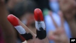 一名女孩星期一在也門反政府的示威中做出勝利的手勢
