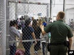 En esta foto provista por el Servicio de Aduanas e Inmigración, personal de la Patrulla Fronteriza vigila a personas que ha sido detenidas por ingresar ilegalmente a EE.UU. en McAllen, Texas, el domingo, 17 de junio de 2018.