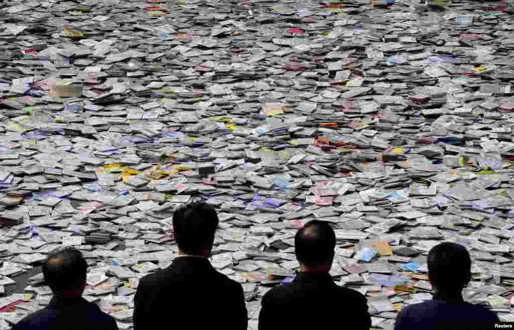 Government officials look on as pirated media, including DVDs, CDs, etc, are placed on the ground before being destroyed, during a campaign against piracy in Taiyuan, Shanxi province, China.