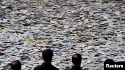 山西太原,人们看着满地的即将销毁的盗版影音光盘等出版品(2015年4月20日)