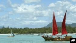 Un bateau mauricien dépasse une réplique du Flor de la Mar, un navire pirate servant d'attraction touriste sur la côte Est de Maurice, 13 novembre 2003.