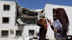 学生走过被轰炸的大学设施