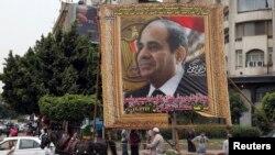 (Foto/dok.) Seorang pria Mesir melewati poster calon presiden Abdel Fattah el-Sissi di Kairo, 6 Mei 2014.
