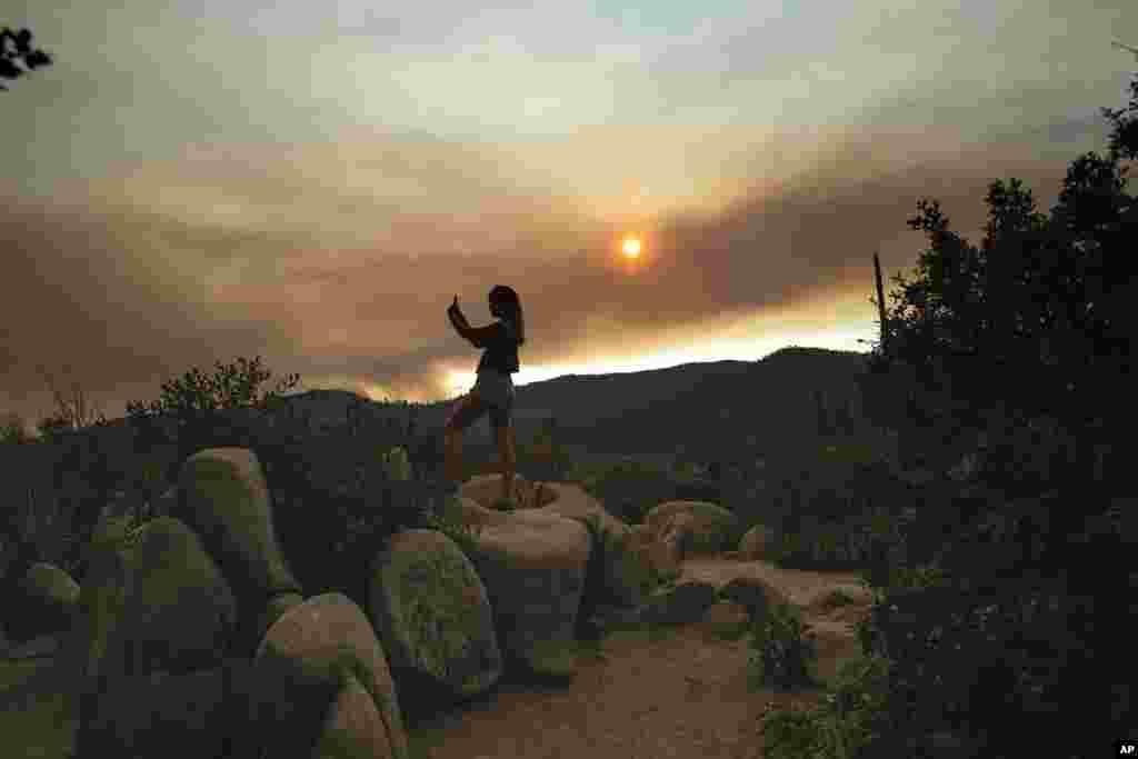 미국 캘리포니아주 요세미티 국립공원에서 한 여성이 국립공원 인근 퍼거슨 산불 현장에서 피어오르는 연기를 찍고 있다. 미국 서부의 대표적인 명승지로 꼽히는 요세미티 국립공원이 2주째 거세게 번지는 대형 산불로 인해 폐쇄됐다.