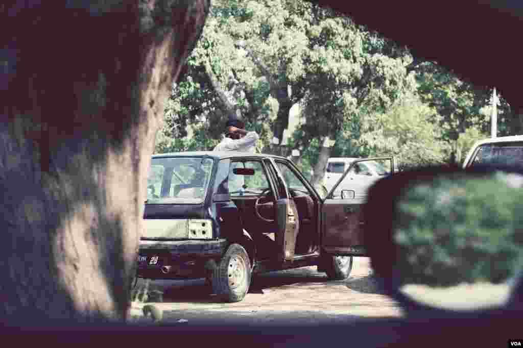 ایک ٹیکسی ڈرائیور اپنی گاڑی کے دروازے کھولے ہوئے کھڑا ہے۔
