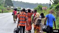 Sekeluarga mengungsi dari distrik Abobo di Abidjan, Rabu (23/2).