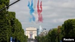 Des Alphajets de l'Armée de l'Air française volent en dégageant une traînées de fumée rouge, blanc et bleu, couleurs du drapeau national français, survolant les Champs-Elysées au cours de la traditionnelle du défilé de jour de la Bastille à Paris, 14 juillet