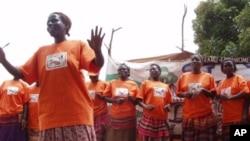 Orange-shirted women promote the health benefits of the orange-fleshed sweet potato during a community theater performance in Uganda.